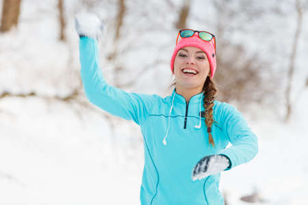 neve palle: Girl has fun throwing snowballs. Relax in winter park. Health nature fitness fashion concept.