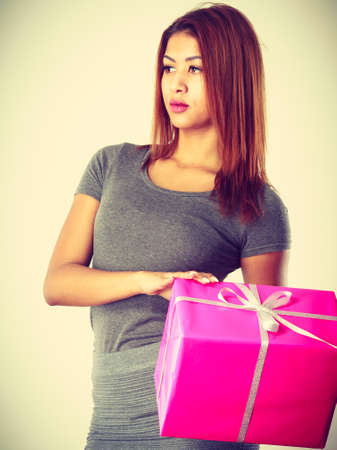 occasions: Occasions gifts people concept. Beautiful woman with pink gift. Young blonde lady wearing nice gray outfit, top and skirt.  Girl is mixed race.