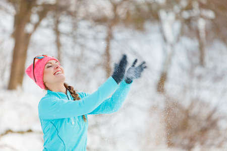 outdoor sport: Girl tossing snow around. Young woman relaxing in the winter park. Health nature fashion fitness concept, Stock Photo