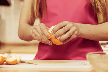 juicing: Woman young housewife in kitchen at home peeling orange fruit for salad or juicing. Healthy eating, cooking, raw food, dieting and people concept.