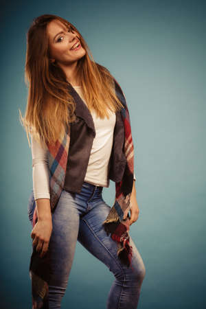 checkered scarf: Fashion clothing concept. Beautiful model posing at studio. Girl is wearing denim trousers and checkered scarf. Stock Photo