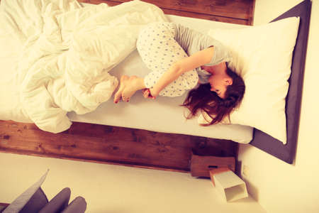 mornings: Mornings people concept. Sleepy woman sleeping in the bed. Attractive lady changing sleep positions.