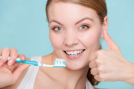 Young woman brushing cleaning teeth. Girl holds toothbrush with toothpaste on it showing thumb up hand gesture. Oral hygiene.
