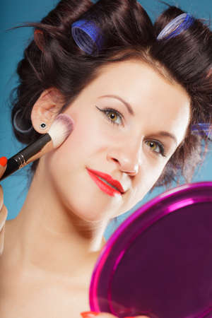 cheekbones: Cosmetic beauty procedures and makeover concept. Woman in hair curlers applying makeup blusher with brush. Girl gets blush on cheekbones, on blue