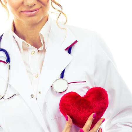Periodic examinations. Cardiology concept. Female cardiologist holding red heart. Doctor with stethoscope and white medical apron uniform. Isolated on white.
