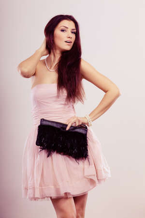 strapless dress: Beauty, fashion and elegant people concept - young brunette slim woman in bright strapless dress holds black clutch bag Stock Photo