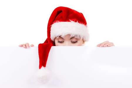over the edge: Woman holding banner sign peeking over edge of blank empty billboard with copy space for text. Girl in santa claus hat looking funny. Christmas advertisement copyspace.