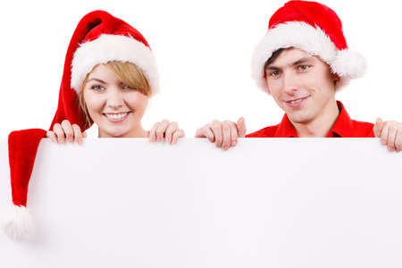 over the edge: Couple holding banner sign with copy space for text, peeking over edge of blank empty billboard. Happy glad girl and boy in santa claus hats. Christmas advertisement copyspace.