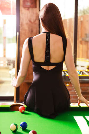 cue sticks: Fashion and fun concept. Young seductive girl posing by billiard pool. Sexy fashionable woman spending time on recreation.