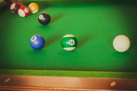 Billiard cue balls on green table. Pool game Stock Photo