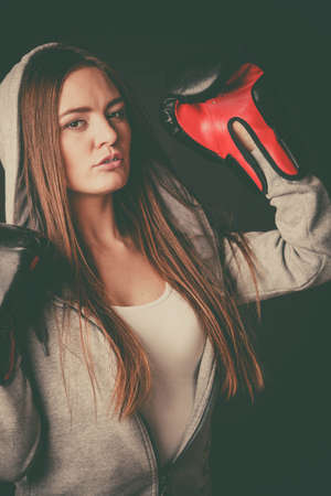 intimidating: Exercising and fighting with opponent. Sportsmanship and strong body. Energetic woman wear sportswear and boxing gloves. Sport and fitness healthy lifestyle.