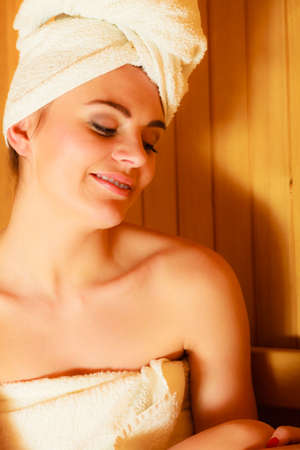 well being: Spa beauty well being and resort concept. Woman in full length white towel lying relaxed in wooden finnish sauna Stock Photo
