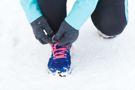 wintry weather: Footwear during winter time and workout outside. Shot of tying sholaces. Sporty trainers for wintry weather and doing exercises.