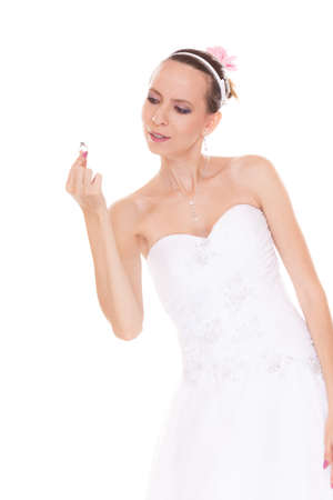 admiring: Bride admiring and looking at engagement ring. Woman in white wedding dress isolated on white background. Stock Photo