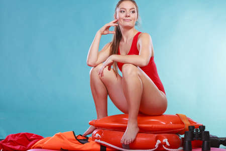 Happy lifeguard sitting on rescue tube buoy and ring lifebuoy. Woman girl having fun. Accident prevention and rescue.