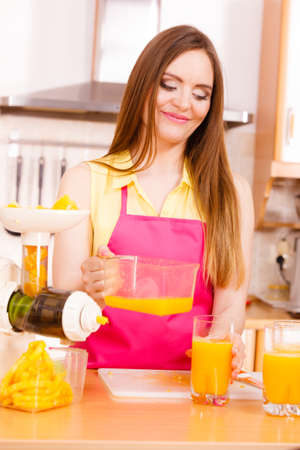 Woman young housewife in kitchen making fresh orange juice in juicer machine, pouring drink from jug in glass. Healthy eating, vegetarian food, dieting and people concept.
