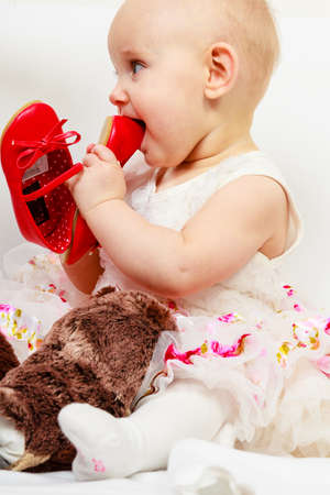 teething: Infant in time of teething. Sweet cute baby girl biting chewing red shoe. Young adorable child wearing white princess dress. Stock Photo