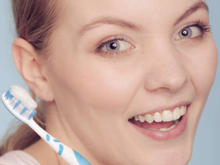 oral cavity: Pretty young girl with brush and toothpaste. Happy woman cleaning her oral cavity caring about dental health. Stock Photo