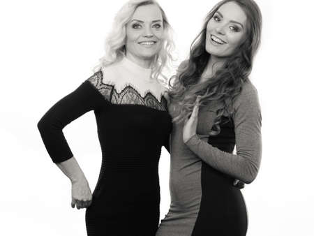 brown haired girl: Generation and relationship. Portrait adult daughter with mother. Two attractive elegant women long curly hairs blonde mom and brown haired girl, b&w photo