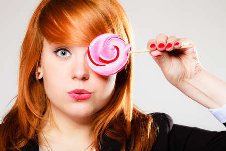 Closeup funny young woman holding candy. Redhair girl with pink lollipop having fun., covering her eye.
