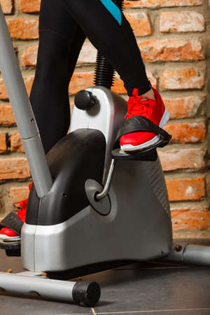 cropped out: Cropped shot of fitness woman working out on exercise bike at the gym. Female exercising legs on bicycle in health club, doing cardio training Stock Photo