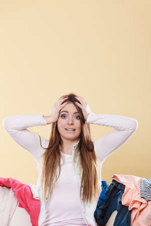 messy clothes: Desperate helpless woman sitting on sofa couch in messy living room with hands on head. Young girl surrounded by many stack of clothes. Disorder and mess at home.
