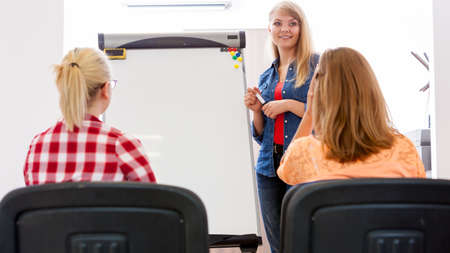 listeners: Teaching, studies course, meeting discussion sharing ideas concept. Woman young teacher near whiteboard and teenage girls students in classroom. Stock Photo