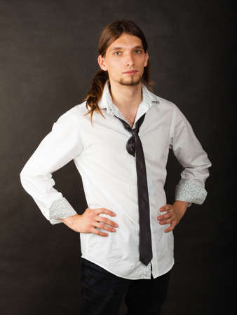 masculinity: Masculinity fashion concept. Man in shirt and tie. Young long haired male on dark background. Stock Photo