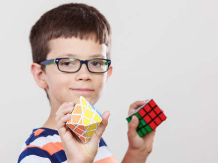 rubik: Portrait of smart cute kid little boy in glasses with magic rubik cube and platonic solid geometric figure. Education.