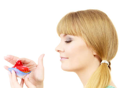 licking finger: Woman holds cake cupcake in hand unhealthy food snack. Bakery sweet eating happiness and people concept. Side view