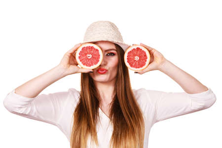 recommending: Woman attractive long hair girl holding grapefruit fruits slices for her eyes on white. Smiling female recommending healthy food. Summer holidays happiness concept