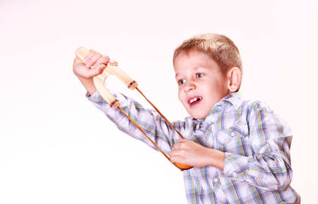 prankster: Nature and free time prankster little boy. Child have fun with  wooden sling shot and fruit aim mandarine.