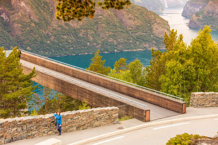 Tourism vacation and travel. Woman tourist enjoying Aurland fjord view from Stegastein viewpoint, Norway Scandinavia.