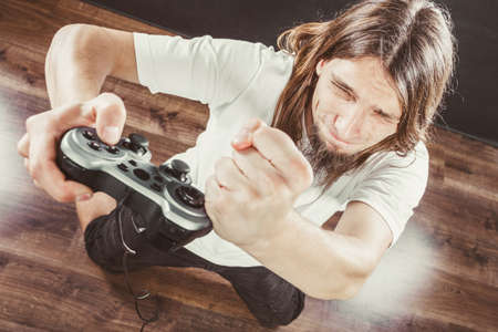playstation: Addiction effects concept. Young unhappy depressed man with pad joystick playing games. Male addicted to console playstation videogames. Stock Photo