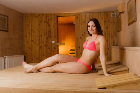 finnish bath: Young woman relaxing in wooden finnish sauna. Attractive girl in bikini resting. Spa wellbeing pleasure.