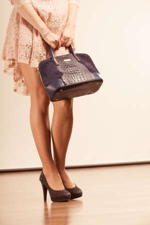 belles jambes: Fashion concept. Female with nice legs holding handbag. Lady is wearing high heels and nice beige dress.