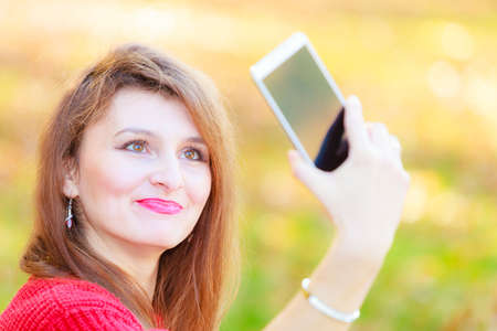 narcissism: Nature outdoor technology social concept. Gorgeous girl taking selfie. Young lady in park takes picture of herself amidst autumnal vegetation.