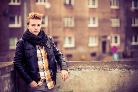 cityspace: Street fashion. Young fashionable man guy with stylish haircut casual clothes posing outdoor on cityspace background. Aged tone