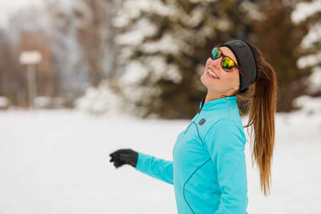 wintry weather: Winter holidays, sporty people concept. Lady spending free time in park. Sporty girl wearing sunglasses enjoying good wintry weather.