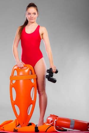 Accident prevention and water rescue. Attractive female model in lifeguard outfit on duty with binocular keeping float lifesaver equipment on gray Stock Photo