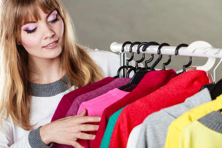 Pretty happy woman choosing which clothing wear from wardrobe. Young undecided shopper girl bought new clothes. Shopping sale concept. Stock Photo