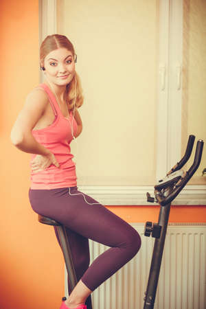 active listening: Active young woman working out on exercise bike stationary bicycle. Sporty girl training at home listening music. Fitness and weight loss concept. Stock Photo