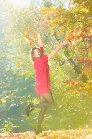 tossing: Young woman tossing leaves. Girl playing in autumnal park. Nature outdoor relax scenery concept. Stock Photo