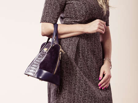 chic woman: Fashion clothing people concept. Chic woman with black, leather handbag. Female wearing elegant dress.