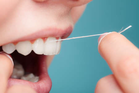 Oral hygiene and health care. Smiling women use dental floss white healthy teeth. Stock Photo