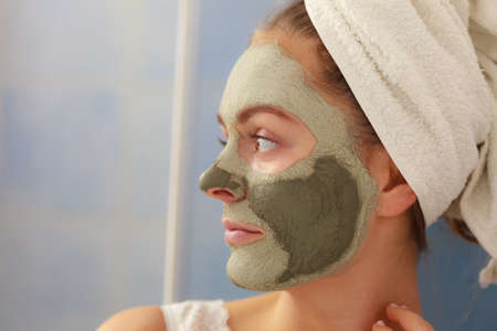 mud girl: Skin care. Woman in bathroom with green clay mud mask on face. Girl taking care of oily complexion. Beauty treatment. Stock Photo