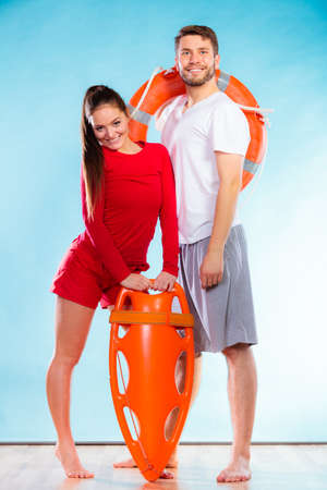 Accident prevention and water rescue. Full length man and woman lifeguard couple holding buoy lifesaver equipment on blue Stock Photo