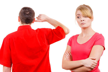 strife: Couple having argument, conflict bad relationships. Angry offended woman and man standing with fingers in his ears not listening Stock Photo
