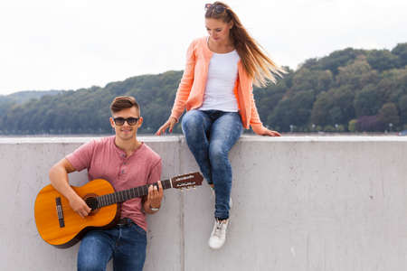 serenade: Love romance music talent passion dating concept. Girl listening to serenade. Young boy playing guitar to his lady.