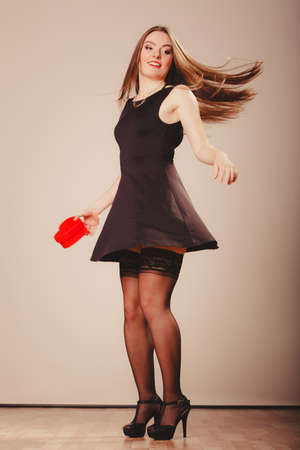 sexualidad: Beauty, sexuality and seductiveness. Young attractive sexy full lenght woman model with red heart box gift present dancing in studio.